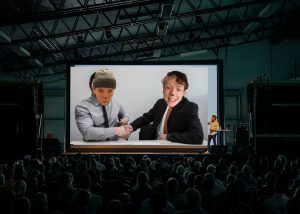 Two business men sit at a desk and shake hands. Their faces have been photoshopped over with pictures of the actors.