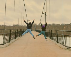Two people jump with their arms and legs spread wide on a bridge leading into a forest.