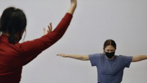Two people wearing masks dance 6 feet apart from each other.