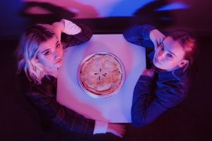 Two girls sit across the table from each other with a pie in the middle.