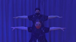 Two people stand in the middle of the screen, one kneeled down lower than the other. They stretch their arms out to the side and look intensely forward. The light overlay is a dark blue.