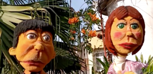 Two Claymation looking characters stand in a garden looking surprised.