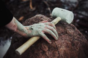 A person puts a mallet down on a rock. Their hands are covered in dirt.
