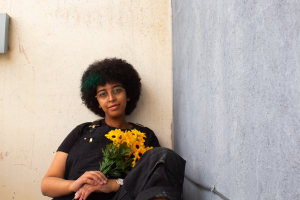 A person sits against a wall holding sunflowers.