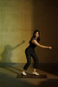 A person dances with their shadow prominently behind them on the wall.