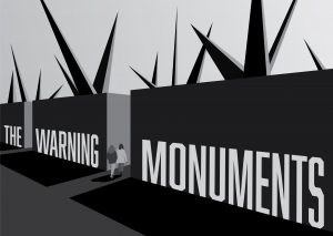 Two people walk between two large block monuments with spikes coming out of the top.