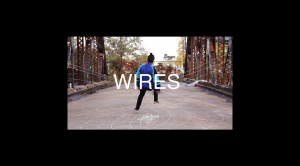 A person dances alone on a bridge connected to wires.