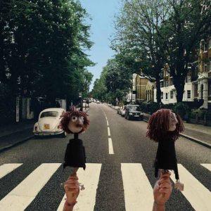 Two puppets walk across abbey road.