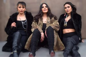 Three people stand against a wall posing in beautiful outfits and beaded jewelry.