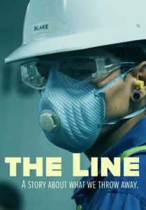 A man wearing protective gear works at a waste treatment plant.