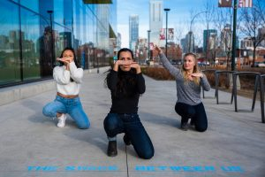 Three people in a triangle formation kneel on concrete outside of a University campus. They are posing with their hands horizontal.