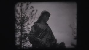 A shadowed statue in a graveyard.