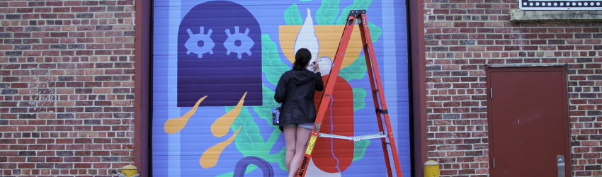 The mural artist stands on a ladder painting the blue, purple, and yellow mural.