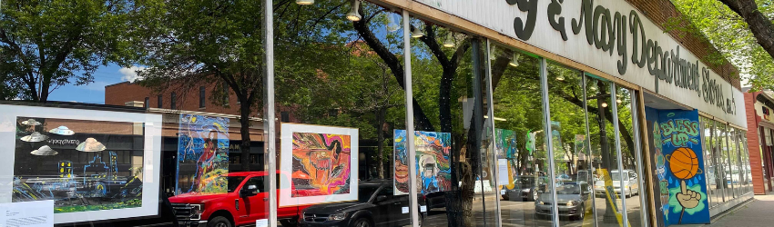 Art works are hanging in the window of the Army and navy.